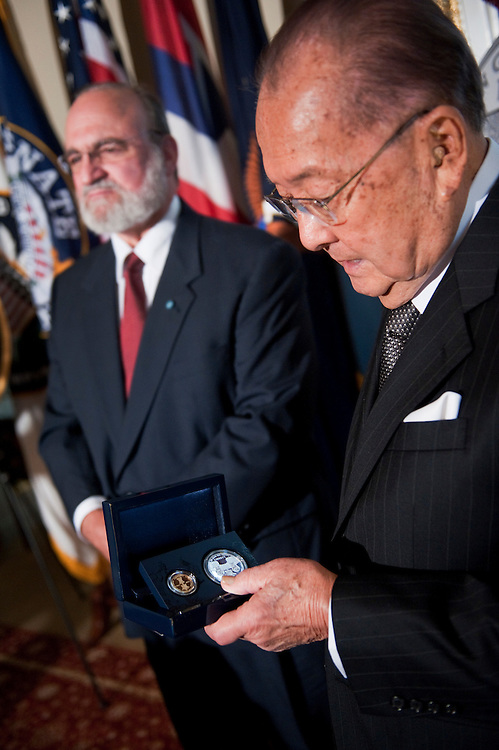 UNITED STATES - SEPTEMBER 19:  Sen. Daniel Inouye, D-Hawaii, right, holds commemorative coins presented to him by the Congressional Medal of Honor Society in the Capitol, as an appreciation of Congress passing legislation 150 years ago that established the Medal of Honor.  Inouye received the Medal of Honor for action in World War II, and Brian Thacker, left, received the Medal for action in Vietnam .  (Photo By Tom Williams/Roll Call)