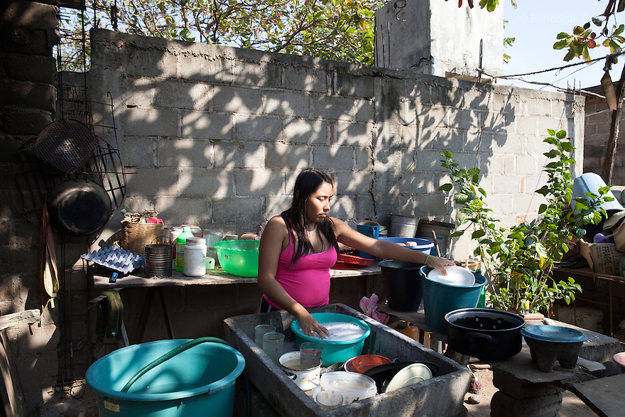 "María José Guerra Santiago washes dishes at her home in Juchitán, Mexico on February 17, 2016. María José, 17, proudly wears a wedding ring – she got married in January, and is five-months pregnant. She looks forward to the respect she says being a married woman – a señora - and having a baby will bring her in the eyes of others. Unlike her husband, she used to love going dancing but now she lives with her in-laws in Juchitán in the southern Mexican state of Oaxaca. ""I won't be able to play like I did before,"" she laments. While Mexico has outlawed marriage under the age of 18, many young girls become unofficial wives and mothers much earlier. In Juchitán, teenage pregnancy is expected, even prized. Mexico ranks first in teenage pregnancies among the member countries of the Organization for Economic Co-operation and Development (OECD). Photo by Bénédicte Desrus"