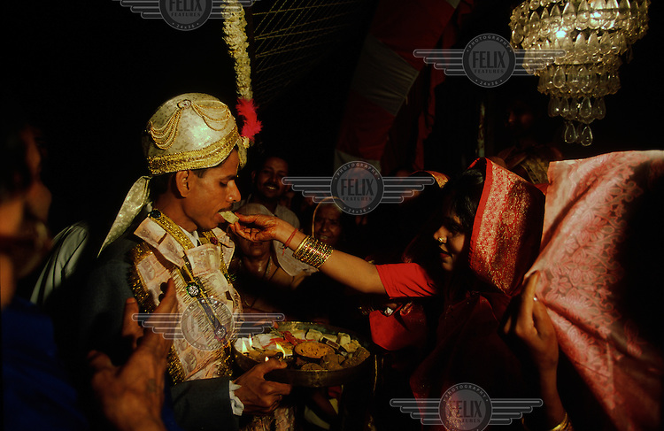 A groom is offered food at his wedding reception.  Around his neck he wears a garland of money which has been donated to the newlyweds as wedding gifts...