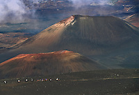 Horseback riders dominated by the massive colorful cinder cones in the crater of HALEAKALA NATIONAL PARK on Maui in Hawaii USA