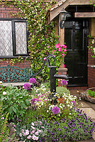 "Front entrance of old house with black picket fence, old pump, black door, patio, flower garden, vines, trees, dogwood, honeysuckle, house name sign of ""The Cottage"", trug of herb plants for inviting welcome, curb appeal entry"