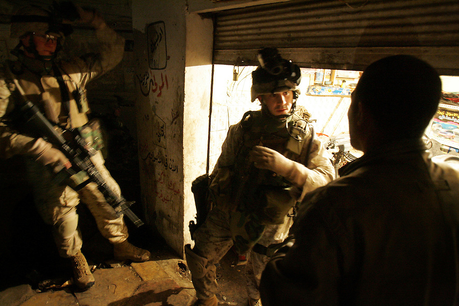 1st Lt. Brian Iglesias questions a man caught breaking the 8:00 pm curfew as Marines with 1st Platoon Golf Company 2nd Battalion 5th Marines carry out a night patrol through the streets of Ramadi, Iraq on January 7, 2005.