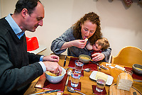 A woman breastfeeds her 20 month old toddler during a family meal at the dinner table.<br /> <br /> 07/02/2013<br /> Hampshire, England, UK
