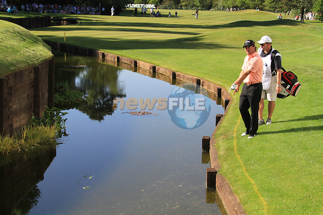 Graeme McDowell points to his ball on the 18th after his second shot hit the BMW corporste hospitality grandstand and bounced into the stream.during final round of the BMW PGA championship 2010 at Wentworth golf club, Surrey England..Picture Fran Caffrey/Newsfile.ie