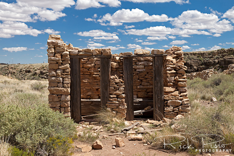 """Quad hole outhouse at Two Guns. Two Guns is located in Arizona, east of Flagstaff, on what was formerly Route 66. Two Guns was originally called """"Canyon Lodge"""" when the National Trail Highway moved westward. Later, the National Trail was re-named Route 66, the site's name was changed to Two Guns, because the proprietor of the facilities located there was one Henry E. Miller, who called himself """"Two Gun Miller."""" During the heyday of Route 66, Two Guns became one of the numerous tourist traps along the way, with a gas station, overnighting accommodations, a food emporium, as well as a zoo. Two Guns went into decline with the building of the Interstate."""