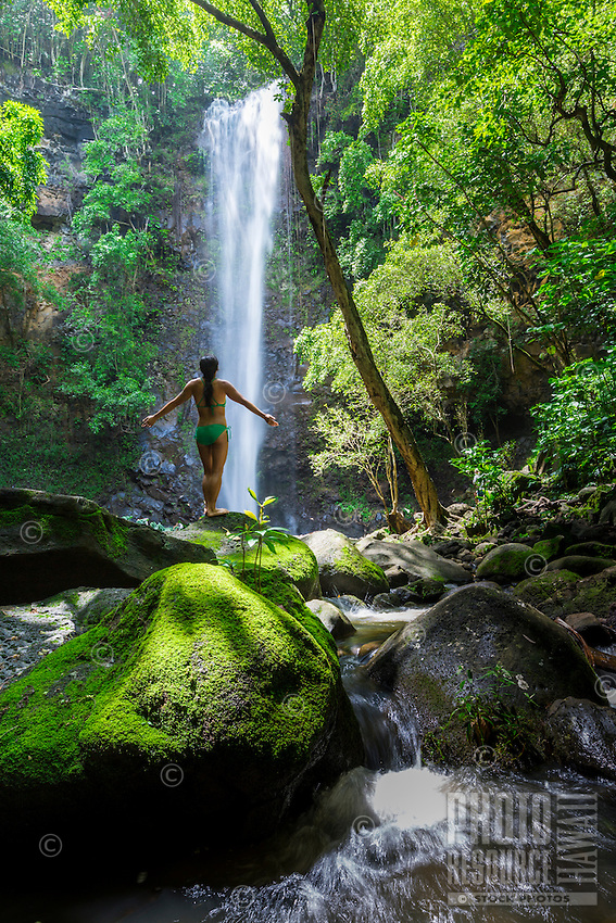 A woman soaks in the sun and spray at Uluwehi Falls, Kaua'i.