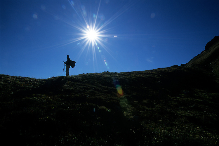 A hiker pauses to enjoy sun in the Kenai Mountains near Hope, Alaska, during a trek through the Chugach National Forest.