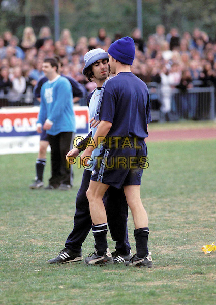 LIAM GALLAGHER & DAMON ALBARN..Ref: 2532/1205f..oasis, blur, fight, playing football, pitch, match, sport, full length, full-length, hats..www.capitalpictures.com..sales@capitalpictures.com..©Capital Pictures..