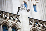 The Washington National Cathedral in Washington, DC is home to more than 200 stone-carved gargoyles.  Here, an old camera gargoyle dots the top of a buttress wall (left center). The purpose of the gargoyles were to both keep evil out of the cathedral and to serve as a water drainage system in torrential rain - the water pours out of the mouth of the gargoyle.
