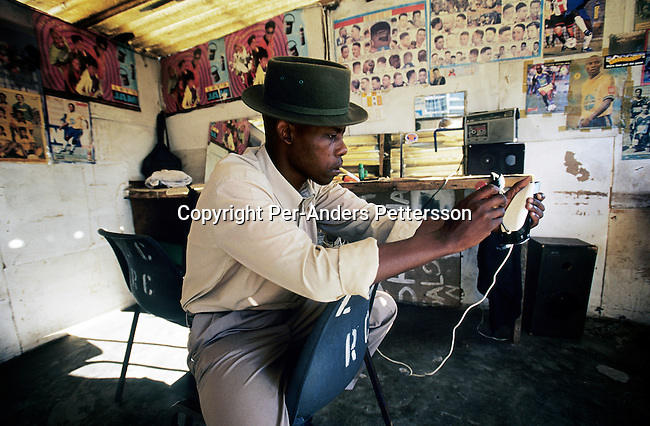 An unidentified barber wait for customers in his shop on July 5, 2001 in Site C Khayelitsha, a township about 35 kilometers outside Cape Town, South Africa. The township has about one million people living there. Khayelitsha is one of the poorest and fastest growing townships in South Africa. People usually come from the rural areas in Eastern Cape province to find work as maids and laborers. Most people don't find work and the unemployment rate is very high. (Photo by: Per-Anders Pettersson)