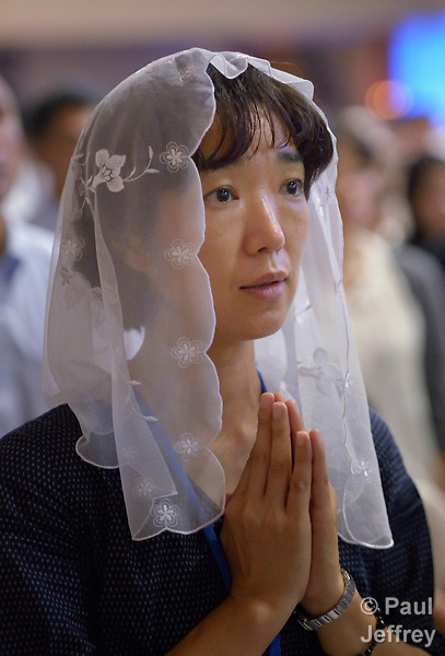A woman prays during a special mass for peace in the Urakami Cathedral in Nagasaki, Japan, on August 9, 2015, the 70th anniversary of the day the United States dropped an atomic bomb on the city. The Catholic cathedral was destroyed by the bombing and rebuilt years later.