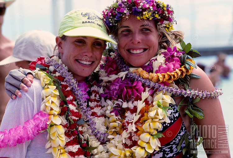 Outrigger canoe racing; paddlers, Mary Smolenski (left) and Katie McCreary (right) of Outrigger Canoe Club, at finish of Women's Molokai to Oahu Race, October 1989, .Kahanamoku Beach, Waikiki, Oahu