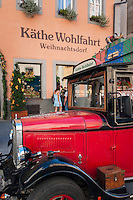 "Germany, Bavaria, Middle Franconia, Rothenburg ob der Tauber: Kaethe Wohlfahrt - company selling Christmas decorations and articles - shop facade and advertising effective oldtimer bus parking in front of the ""Christmas Museum"" 