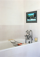 A plasma screened television is positioned at a comfortable height in the tiled wall of this small bathroom