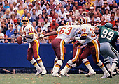 Washington Redskins quarterback Doug Williams (17) looks to pass the ball to running back George Rogers (38) during the game against the Philadelphia Eagles at RFK Stadium in Washington, DC  on September 13, 1987.  Blocking for Williams is Redskins left guard Raleigh McKenzie.  Eagles' right defensive tackle Jerome Brown (99) tries to pressure Williams. The Redskins won the game 34 - 24.<br /> Credit: Ron Sachs / CNP