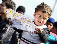 """Pictured: A young boy holding a piece of paper with a """"Open borders Macedonia""""  slogan Thursday 03 March 2016<br /> Re: Migrants have closed off the railway track at the Greek Fyro Macedonian border in Idomeni, Greece,"""