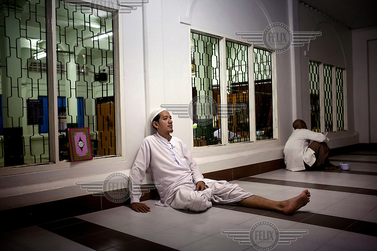 A man rests after praying in the Pakistan Mosque in Pattani. /Felix Features