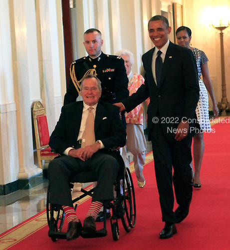 "Former United States President George H.W. Bush and U.S. President Barack Obama at a ceremony in the East Room of the White House to present the 5,000th ""Daily Point of Life"" on July 15, 2013. <br /> Credit: Dennis Brack / Pool via CNP"