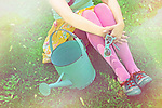 Faceless close-up of a young girl sitting on lawn wearing pink tights holding sunglasses enjoying summery weather with a retro feel and watering can