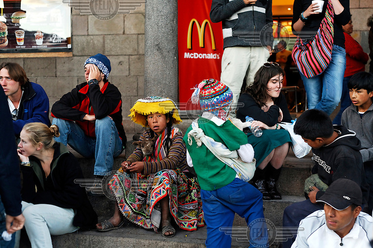 Tourists and Indians, some wearing traditional dress, sitting on some steps outside a McDonalds take away restaurant in the Plaza de las Armas. Inca culture has become a major attraction bringing tourists to the region...