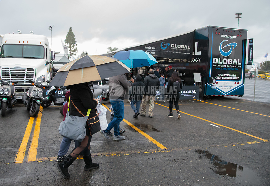 Feb 10, 2019; Pomona, CA, USA; NHRA fans hold umbrellas in the rain as they walk past the pit area of funny car driver Shawn Langdon during the Winternationals at Auto Club Raceway at Pomona. Mandatory Credit: Mark J. Rebilas-USA TODAY Sports