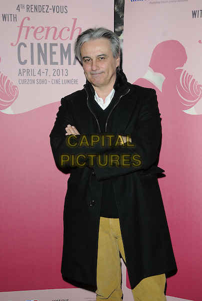 "Gilles Bourdos.attended the ""Renoir"" UK film screening as part of the 4th Rendezvous with French Cinema Season in London, Curzon Soho cinema, Shaftesbury Avenue, London, England, UK, .6th April 2013..half length black coat arms folded crossed smiling .CAP/CAN.©Can Nguyen/Capital Pictures."