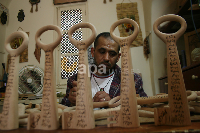 Palestinian Nasser Flefel, 37, carves wooden keys, representing the keys to the houses of Palestinian refugees which were left in 1948 and a symbol for the right of the return of refugees, in his wood-carving shop in Gaza City.  Hundreds of thousands of Palestinians were uprooted during the 1948 war over Israel's creation, and some 4.5 million Palestinian refugees and their descendants are scattered across the region today. Israel is marking its 60th anniversary today. Israel celebrates its 60th birthday, an anniversary that for the Palestinians, more divided than ever before and hungry for a state of their own, marks a 'catastrophe'.