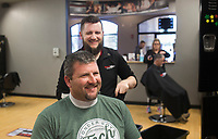 """Stylist Jon Danger (center) gives a haircut to Nick Willbanks of Fayetteville (left), Monday, March 23, 2020 at Sports Clips Haircuts in Fayetteville. Check out nwaonline.com/200323Daily/ for today's photo gallery.<br /> (NWA Democrat-Gazette/Charlie Kaijo)<br /> <br /> Monday is the last day that hair salons, tattoo shops, nail salons and massage parlors are permitted to stay open. He said he heard the news while watching Gov. Asa Hutchinson's address to the state. <br /> <br /> """"[It] sucks man. My job and security. Still got bills to pay. [It's] the unknown of when we're coming back. I'm on a weird fence of do I need a job? Or do I want people to die?"""" he said."""
