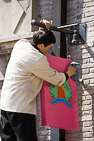 Man cleans sign for Shanghai Tang designer clothes shop, owned by David Tang, Xintiandi, China