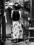 Rear view of female model in a hat passing through a gate