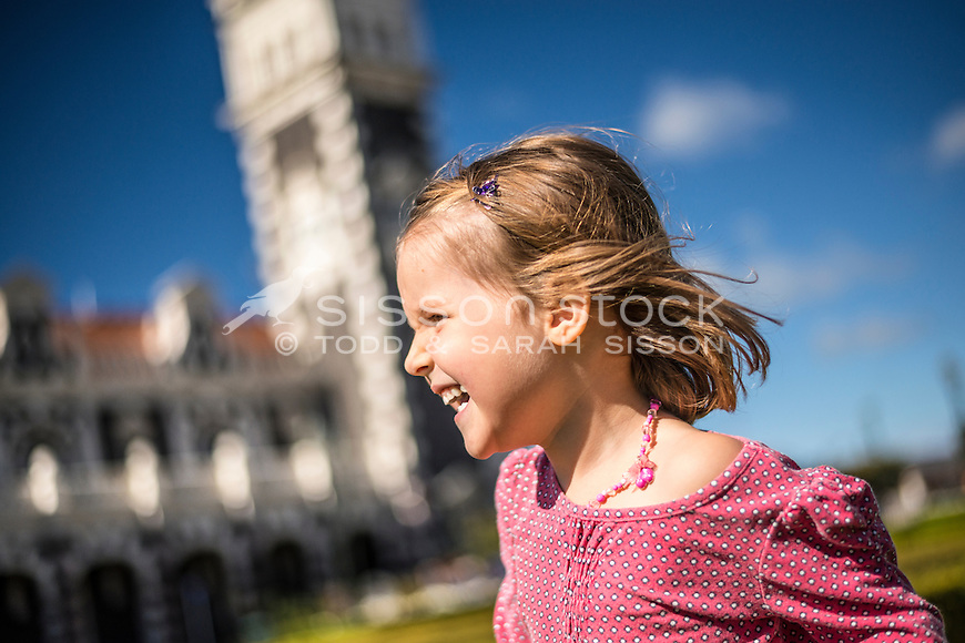 Young girl (5 years) smiling in the gardens outside the Dunedin Railway Station on a sunny summers day, Otago, South Island, New Zealand - stock photo, canvas, fine art print