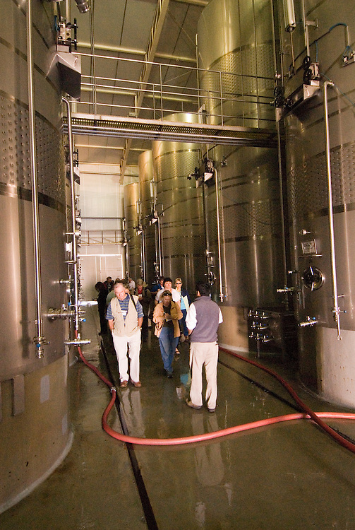 Chile Wine Country: Stainless steel tanks at Undurraga Winery, Vina Undurraga, near Santiago.  Tour group on wine tour..Photo #: ch431-33904..Photo copyright Lee Foster, 510-549-2202, www.fostertravel.com, lee@fostertravel.com.