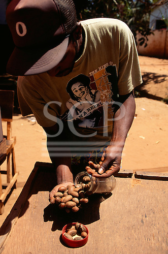 The Gambia. Market trader selling kola nuts from a glass jar; Boss hat, rasta t-shirt.
