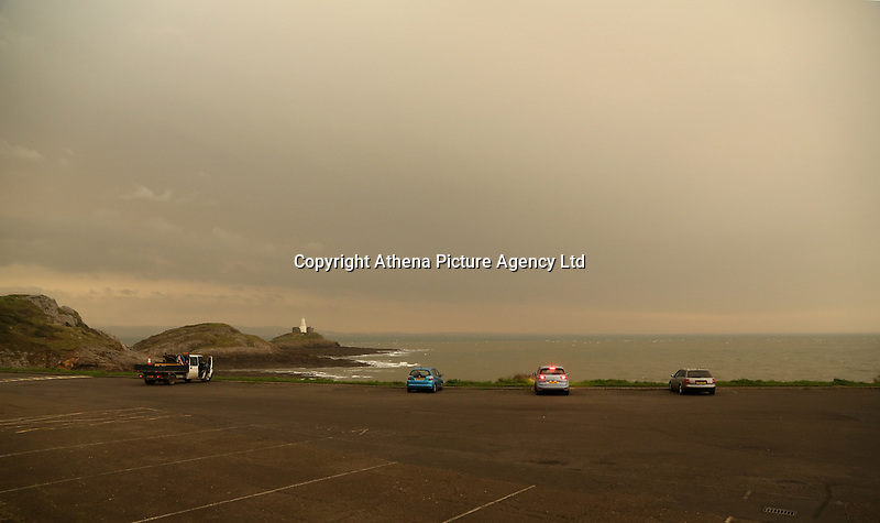 """An unusually orange cloud over Mumbles Lighthouse at the seaside village of Mumbles near Swansea, UK. Monday 16 October 2017<br /> Re: Remnants of Hurricane Ophelia are expected to bring strong gusts of wind to Wales when it hits Britain's shores.<br /> The hurricane, making its way from the Azores in the Atlantic Ocean, will have weakened to a storm when it arrives.<br /> A Met Office amber """"be prepared"""" warning has been issued in some areas bringing """"potential danger to life""""."""