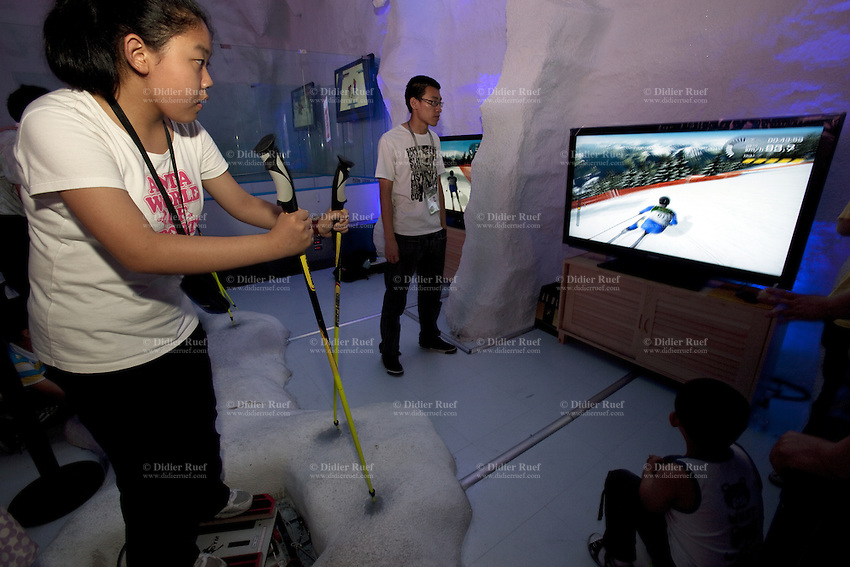China. Shanghai. World Expo. Expo 2010 Shanghai China.  China Pavilion. A chinese girl is playing a video game displayed on a large flat television screen in the Heilongjiang pavilion. She pretends to be a ski competitor during a downhill race in the mountains. 25.06.10 © 2010 Didier Ruef