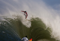 "Evan Slater (red) catches the wave over Darryl ""Flea"" Virotsko (white) at the 2010 Mavericks Surf Contest in Half Moon Bay, California on February 13th, 2010."