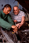 Vocational High School Automotive Repair class older maie instructor working with male student vertical