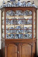 A collection of miniature blue and white K'ang Hsi (1662-1722) porcelain in typical Dutch 18th century oakwood display cabinet