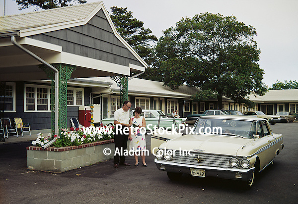 Americana Motel, Bass River, MA.  Couple reading a map at the entrance to the motel. 1963