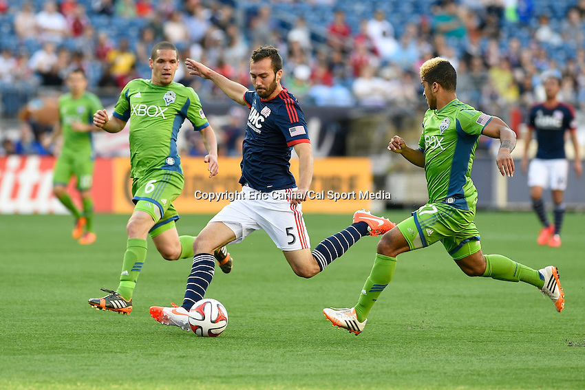 May 11, 2014 - Foxborough, Massachusetts, U.S. - New England Revolution defender A.J. Soares (5) kicks the ball with Seattle Sounders FC midfielder Osvaldo Alonso (6) and defender DeAndre Yedlin (17) in pursuit during the MLS game between the Seattle Sounders FC and the New England Revolution held at Gillette Stadium in Foxborough Massachusetts.  New England defeated Seattle 5-0   Eric Canha/CSM