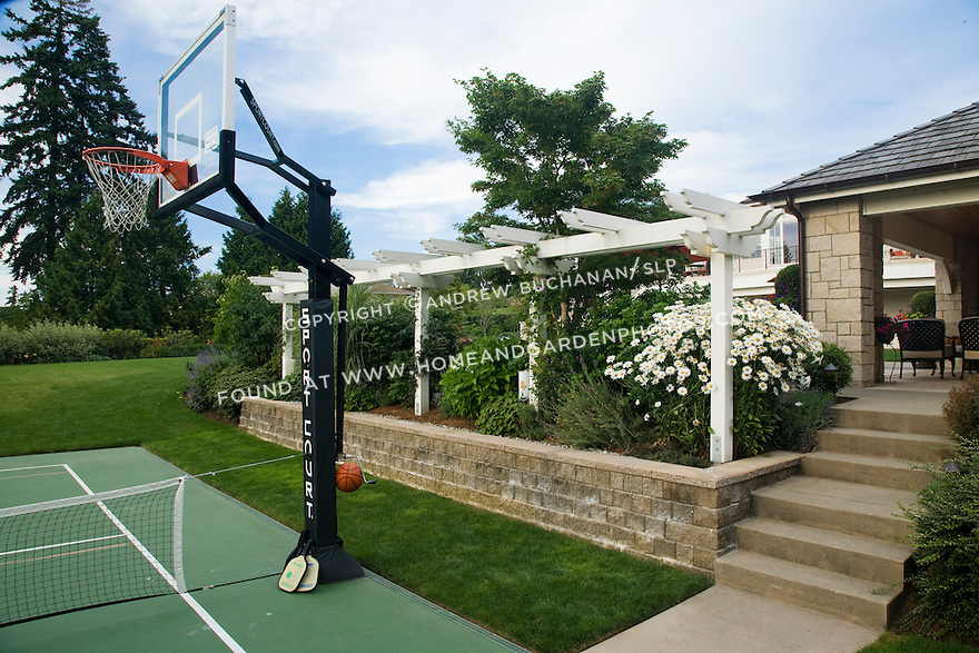 This fantastic yard and poolside outdoor living area in a suburban community east of Seattle, includes a sport court for active play by kids on the lower level of the yard, and a few short steps up to the upper level containing the swimming pool  and poolside cabana building, screened from the lower court area by the hedge of shrubs and grasses, and the overhead trellis.