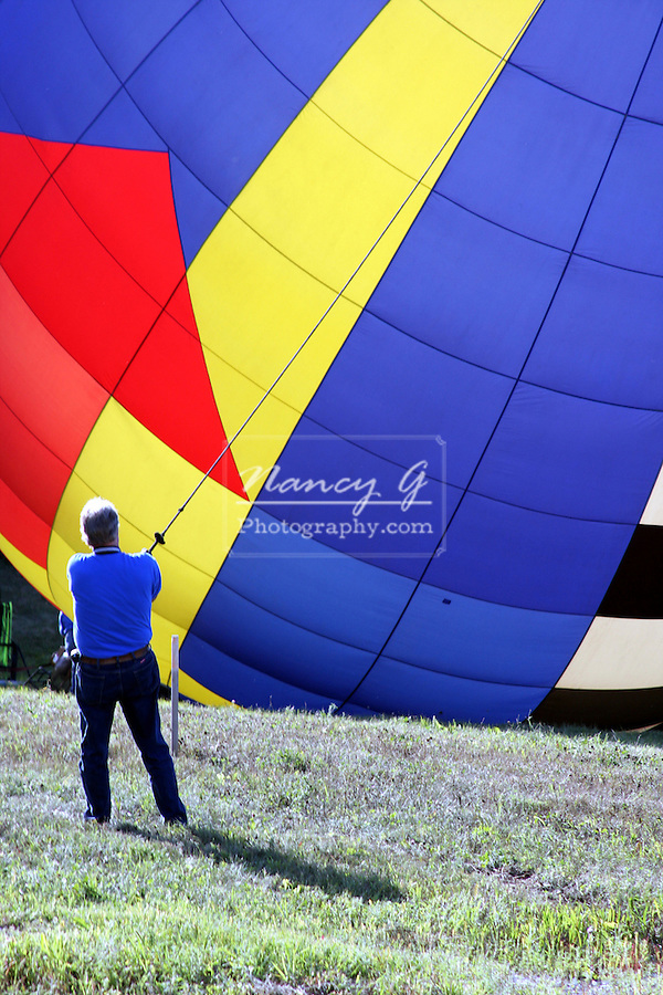 A hot air balloon is being held down by a person and anchored for safety