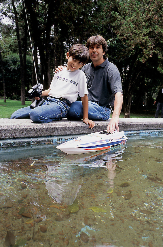 Father and Son enjoy playing with their remote controled boat in Parque Lincoln, Polanco, Mexico City, September, 2005