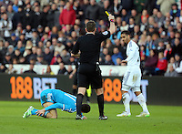 SWANSEA, WALES - FEBRUARY 07: Kyle Naughton of Swansea (R) sees a yellow card by match referee Phil Dowd (C) for his foul on Adam Johnson of Sunderland (L) during the Premier League match between Swansea City and Sunderland AFC at Liberty Stadium on February 7, 2015 in Swansea, Wales.
