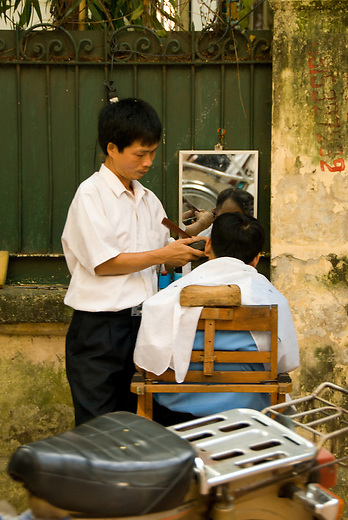 A man gets his hair cut on the side of the street in Hanoi, Vietnam.  Personal care services are commonly performed out on street sidewalks.