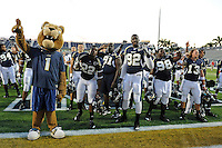 9 October 2010:  FIU's mascot, Roary, and team members Markieth Russell (22), Jordan White (91), Paul Crawford (92), Jerrico Lee (98), and Wesley Carroll (13) gather near the student section for the playing of the alma mater after the FIU Golden Panthers defeated the Western Kentucky Hilltoppers, 28-21, at FIU Stadium in Miami, Florida.