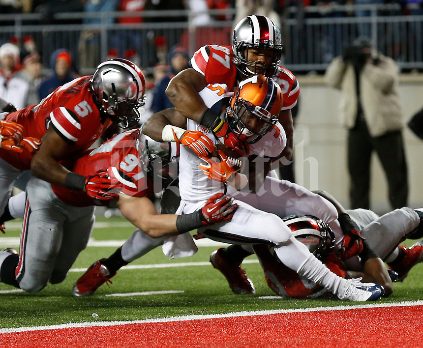 A slew of Buckeye defenders, including defensive lineman Joey Bosa (97) and linebacker Joshua Perry (37) tackle Illinois Fighting Illini running back Donovonn Young (5) at the goal line during the second quarter of the NCAA football game at Ohio Stadium on Nov. 1, 2014. (Adam Cairns / The Columbus Dispatch)