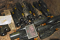 old bottles in the cellar chalk board domaine comte senard aloxe-corton cote de beaune burgundy france