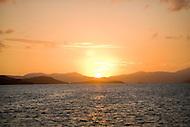 Looking across the open ocean, the sun sets over the US Virgin Islands.