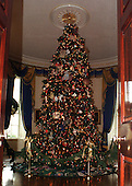 The centerpiece of the Blue Room is the official White House Christmas Tree, an 18 1/2 foot Noble Fir, from the Hedlund family's Christmas Tree farm near Martin, Washington (State) on December 6, 1999.  The tradition of a thematic tree began in the early 1960s and is continued this year with ornaments that honor our colorful heritage. American crafts were designed and created by expert craftsmen, replicating objects and scenes from our history.  Dollmakers honored our forefathers and contemporary heroes with dolls made in their images, such as Benjamin Franklin, Amelia Earhart, Albert Einstein, and Rosa Parks.  Tinsmiths have hand-forged ornaments indicative of their colonial trade, such as miniature Revere lanterns and candlesticks.   The green velvet tree skirt was handmade by individuals from each of the 50 states, territories and the District of Columbia in celebration of the Clinton family's first holiday season at the White House..Credit: Ron Sachs / CNP